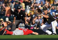 READY LEATHER:    Pirates infielder John Jaso waits for a throw as Red Sox infielder Brock Holt slides into first base on a pickoff attempt in the first inning on March 28 at McKechnie Field in Bradenton, Fla.