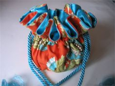 This pretty jewelry tote is done in an Amy Butler cotton print. Royal Garden in clay. The lining is a bright turquoise. A twisted turquoise satin cord is used fir the closure. This little beauty has 8 individual pockets for rings, earrings, watches, chains and things. The generous center section will hold larger pieces such as chunky pendants or bracelets. Extended opening 9+  Closed 5 tall There are many uses for this bag at home or traveling including but not limited to: Jewelry organizer…