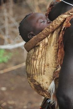 ˚Me'en (Bodi) baby on his mother's back - South Ethiopia