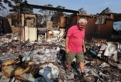 Local resident Alan Seaman walks through the remains of his home.   A state of emergency has been declared in New South Wales (NSW) state, Australia's most populous.  New South Wales Rural Fire Service. (REUTERS/David Gray) less