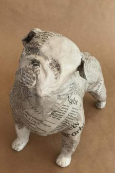 This was a custom dog. The buyer wanted an English Bulldog in black and white, covered with newsprint. The pose he wanted was the standing dog looking slightly up and in a confident posture. This free standing English Bulldog is made of paper, wire, and archival glue. I like to personalize custom orders when possible. As he was going to a home in New York City, I thought itd be fun to cover it with the New York Times. As with each of my one-of-a-kind dog sculpture, I begin with a wire…