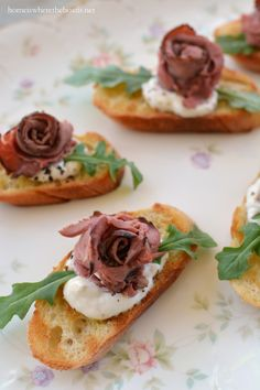"""Rose"" Beef Bites are a pretty way to serve a roast beef canapé for a party! This is my favorite kind of appetizer since you can mix your horseradish cream and assemble the beef in advance, rolling into a small rosette. To make horseradish cream, mix 1/2 cup sour cream or creme fraiche with 1 tablespoon grated horseradish and salt and pepper. When it's party time, toast your baguette slices, assemble and serve with a peppery arugula leaf."