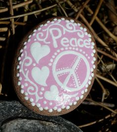 Pretty hand painted Great lakes beach stone. Pink and white with hearts, a peace sign and the word PEACE painted on it. Perfect unique gift