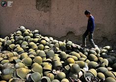 Afghan boy walks next to a pile of Russian-made helmets in the Panjshir Valley, some 100km (63 miles) north of Kabul, Afghanistan August 10, 2005. Pictures of the month August 2005 REUTERS/Ahmad Masood