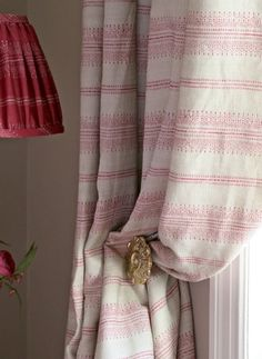 Camille Fabric A fresh linen union fabric featuring stripes of various widths formed from small scale geometric shapes and dotted lines, printed in raspberry on a light beige ground.