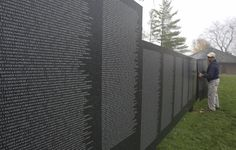 Clint Burnell installs a panel Wednesday to create a replica of the Vietnam Wall memorial at Rotary Hill as part of Naperville's third Healing Field of Honor Veterans Day display. The wall has the names of all 58,000 military members who died in Vietnam, including 11 from Naperville.
