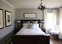 Cool dark wood sleigh bed. Love the picture frame layout. (and the reading chair)