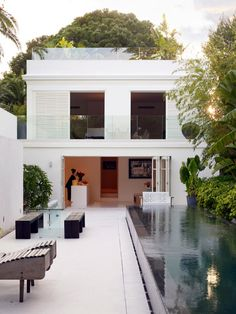 John Rochas patio and pool oasis in Provence | Modern infinity pool with white concrete flooring, lush landscaping and privacy wall, living room opens to backyard via accordion glass doors