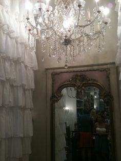 A gorgeous mirror, dressing room and chandelier in a boutique in Panama City Beach