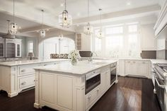 White and brown kitchen features white shaker cabinets topped with white marble fitted with a deep farmhouse sink and a deck mount faucet placed under three windows.