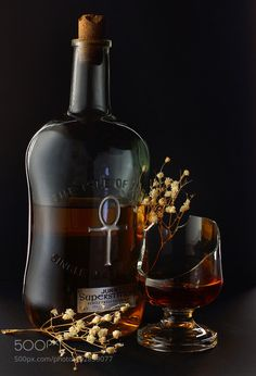 Still-life from a bottle of whiskey broken glass and dry flowers on a black background by more_lena