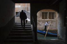 Man walking near gondola, classic Venician scene.