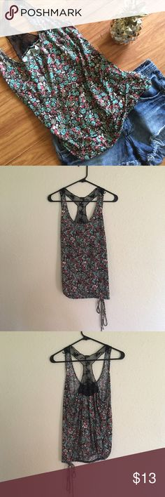 American Rag Floral Tank Top EUC floral tank top with lace detail on the back. Has a loose fit with an adjustable bottom to make the bottom looser or tighter to your preference. No visible flaws or defects.   ⭐️Sorry I don't do any trades.  ⭐️ I'm always open to reasonable offers.  ⭐️ Bundle 2 or more items to save! American Rag Tops Tank Tops