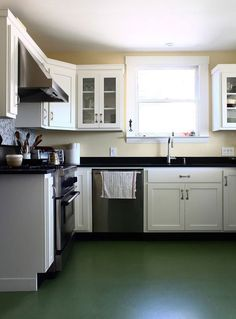 modern cottage kitchen, marmoleum floor, like the light yellow walls w/ white cabinets, dark counter & low backsplash of same material / writer Mary Roach's house