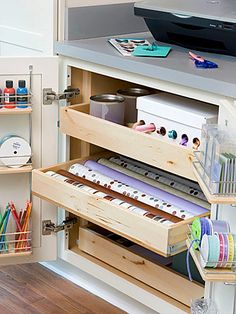 Crafts Cabinet Hideaway- One cabinet in a home office can hide crafts supplies but keep them within reach. These pullout drawers are perfect for holding wrapping paper, ribbon, and tins of other supplies. Use the inside door space too, perfect for housing paint jars, vases filled with color pencils, and more ribbon. The counter holds a copier for enlarging patterns.