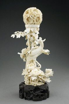 Exquisitely carved ivory puzzle ball with a phoenix. The peonies, the phoenix and the puzzle ball all represent femal.
