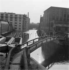 """Caption: """"Regents Canal in Camden Town, looking south west from an elevated viewpoint at Hampstead Road Lock, and showing a roving bridge carrying the towpath across the canal in the foreground, with some empty industrial barges and canal warehouses beyond."""" #london #canal #camden #lock #hampstead #road #bridge #market #gilbeys #gin #interchange #warehouse #barge #lighter #dock"""