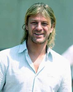 Sean Bean with a beard and long hair white shirt.  Nice smile.