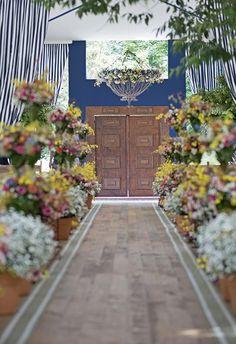 Entrada da cerimônia de casamento no campo - decoração em azul e branco - arranjos de flores em azul, amarelo, rosa e laranja - porta de madeira ( Foto: Isabel Becker )
