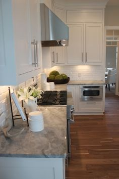 source: The Fat Hydrangea website Parade of Homes - Lovely kitchen with white shaker cabinets paired with Alpine White Granite countertops and white brick backsplash.