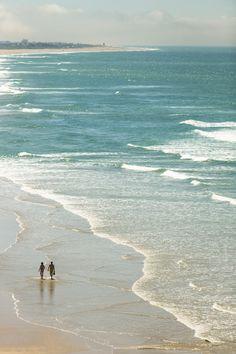 A couple walk on the beach at Conil de la Frontera, in Andalucia.