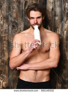Bearded man, short beard. Caucasian sexy macho man with moustache show six packs and abs on muscle torso holding bottle with kefir or yogurt on brown vintage wooden studio background - Shutterstock Premier