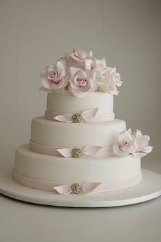 Classic roses tinted with a hint of pink finish off -this beautiful cake.  sugar ribbon fastened with diamonte button-gorgeous