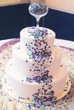 "Purple, blue, and teal edible confetti dots spill out of a champagne glass topper down this otherwise simple white wedding cake. Such a fun idea! Maybe for a New Year's Eve wedding...? Love that they sprinkled more of the ""confetti"" onto the display table for continuity. And I dig that muted coordinating watercolored paisley-looking vintage scarf over the (again) plain white tablecloth as well."