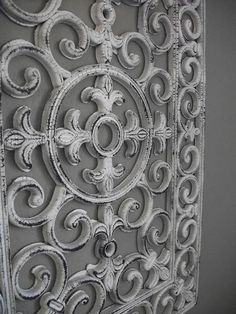 Floor mat painted to look like wrought iron and used as wall decor