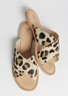 Totally rad, ponyhair sandals featuring a leopard print with two thick crisscross straps and a slip-on design.