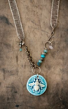 This one of a kind necklace features a beautiful ceramic pendant handmade by Nan Emmett of Spirited Earth and is accented with mottled turquoise