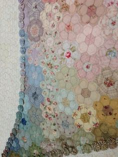 Japanese hexagon quilt.  There is a picture of the whole quilt on this page.  What I like is the yo-yo's outlining the center heart and the hexagon border.  I would prefer a smaller center with less white background surrounding the 'swoopy' heart.  Just make it a smaller quilt.