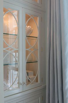 Marcus Design glass knobs, glass shelves, lighting and detailed glass front doors on built-ins