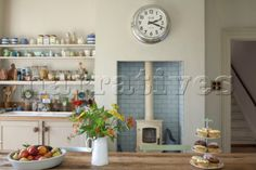 Cut flowers and cakes on table in kitchen with recessed wood burner and open shelving - if this was white and not cream it would risk being shabby chic