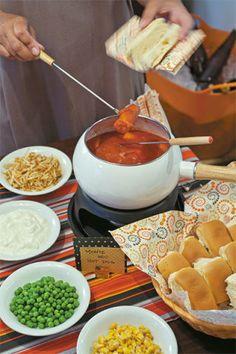 Tomates sem pele em lata, batidos no liquidificador com alho, sal e manjericão fresco, compõem o molho para as salsichinhas. Como acompanhamento, sirva batata palha, maionese, milho, ervilhas e o que mais desejar.