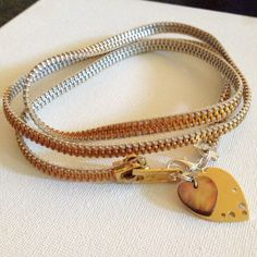 White & gold colored zipper necklace with 2 different heart charms attached