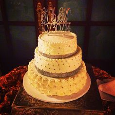 Three tier wedding cake with little pearls cascading designs ball over the first-tier diamond jewels around the second-tier with pearls and the third tier has the diamond tiara around it with more pearls and designs
