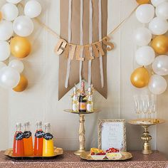 Toast the New Year under a festive DIY banner. Use gold glitter paper and stencils to cut the letters, then use a hole punch and ribbon to string together the sign. Frame your bottles of champagne with white and gold balloons to complete the toast-worthy occasion./