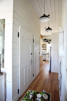 MMH-could go with the low end hollow core doors and later apply a thin wood veneer and paint over to get the farmhouse door effect; love the lights too