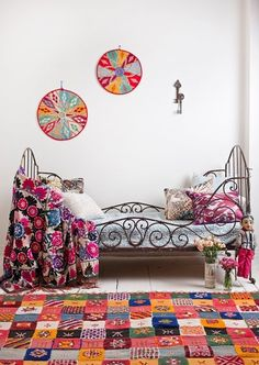 Beautiful Bohemian Chic bedroom with colorful textiles displayed against crisp white walls and floors  (via Home and Decor)