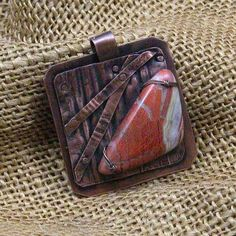 """Handmade fold formed copper and jasper pendant features a semi-precious jasper gemstone feature mounted on copper. Pendant is 1 1/2"""" wide by 2"""" high and can be worn on a chain or slide. Add a necklace"""