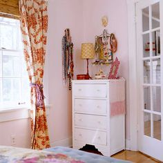 A Vintage-Chic Cottage Personalized Pieces:   Let your treasured flea-market finds or family heirlooms tell a story. In this room, vintage jewelry gives the narrow wall a punch of pizzazz.