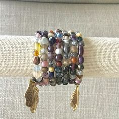 A Boho style earth tone beaded memory wire bracelet that will wrap around any wrist. A wide variety of bead types and colors such as purple, brown, black, wood, clear, stone, white and more. Seven wire loops. Bronze toned leaf charms are attached to each wire end to add a special
