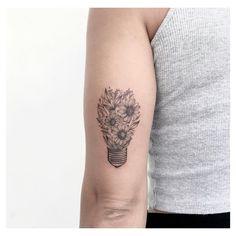 Tatuagem criada por Ana Luiza de Maceió. Flores em formato de lâmpada na parte de trás do braço.