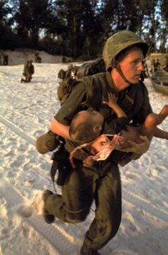 Caption from LIFE   A corpsman attached to the Marines, who took the little boy from her, cradles him in his arms and double-times across the beach under heavy Vietcong sniper fire so he can treat the baby in safety.