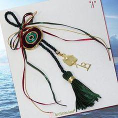 Ελληνικό χειροποίητο γούρι 2018. Αποτελείται από ένα μεταλλικό μάτι σε χρυσό χρώμα με πράσινο και μπορντό σμάλτο, δεμένο σε μία κυπαρισσί φούντα με σατέν κορδέλες. Το γούρι είναι διακοσμημένο με ένα σπιτάκι και την ημερομηνία του '18, ως σύμβολα καλής τύχης. Ιδανικό δώρο Χριστουγέννων και πρωτοχρονιάς. Metal evil eye with bordeaux and green enamel decorated with satin ribbons a metal little house a '18 date and a tassel as a Christmas good luck charm. Great gift idea for a happy new year. Xmas Decorations, Tassel Necklace, Ribbon, Charmed, Detail, Handmade, Gifts, Beauty, Jewelry