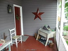 Love the red painted porch and matching door  Love the crude tables  Love the red star  Enjoy the gray siding