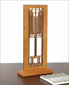 "This Frank Lloyd Wright Tree of Life Hardwood Mini Screen measures 11.12"" in height by 5.5"" wide x 2"" deep (including attached stand). Ideal for table, desk or windowsill display. Each screen has been precision laser-cut and comes with a cherry veneer finish. This Frank Lloyd Wright Tree of Life design is inspired by an art glass window in the Darwin D. Martin House (Buffalo NewYork, 1905)."