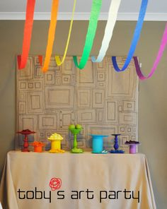 food table - Colored platters to match foods. Frame backdrop drawn on contractor's paper. Streamer swags above each color of food. Canvas drop cloth tablecloth.