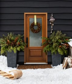 For the winter season, designer Grace Castaneda places tall urns stuffed with lush evergreen boughs and pine cones on either side of her front door for a warm welcome. | Photographer: Donna Griffith